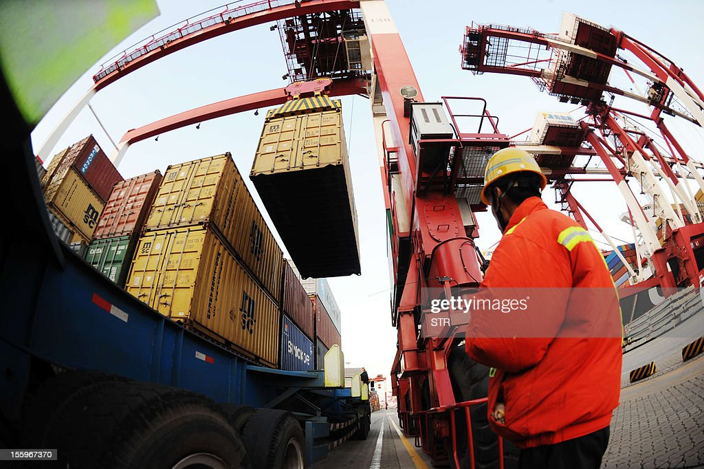 This picture taken on November 7, 2012 shows a port worker monitoring the unloading of containers on to the trucks at the port of Qingdao in northeast China's Shandong province. China's export growth accelerated in October, the government said on November 10, adding to evidence the world's second-largest economy is bouncing back as the ruling Communist Party chooses new leaders. CHINA