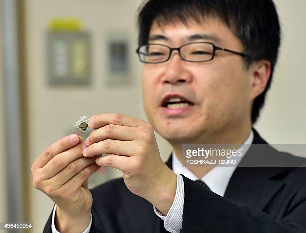 This picture taken on November 9 2015 shows Japan's University of Tokyo professor Takao Someya displaying an ultrathin flexible thermal sensor on a...