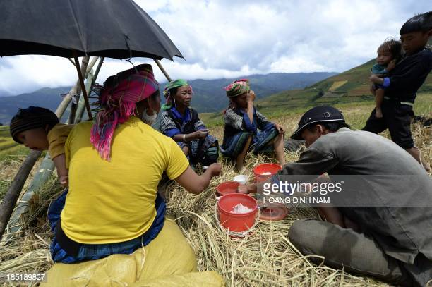 This picture taken on October 1 2013 shows a Hmong ethnic hilltribe family having lunch during a rice harvesting on a terrace rice field in Mu Cang...