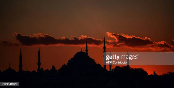 TOPSHOT This picture taken on October 10 2017 shows Suleymaniye Mosque and New mosque during sunset over the historical Eminonu district in Istanbul...
