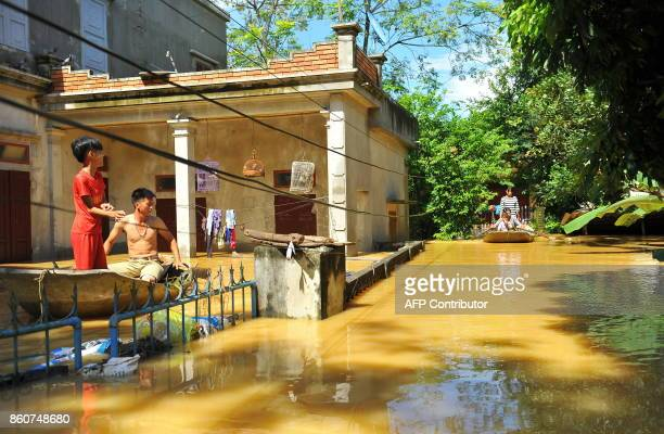 This picture taken on October 12 2017 shows a villagers using boats to move around at a flooded village in the northern province of Ninh Binh The...