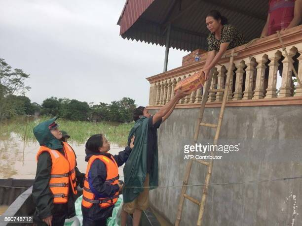 This picture taken on October 12 2017 shows local officials and rescuers handing over a box of instant noodles to a floodaffected family in the...
