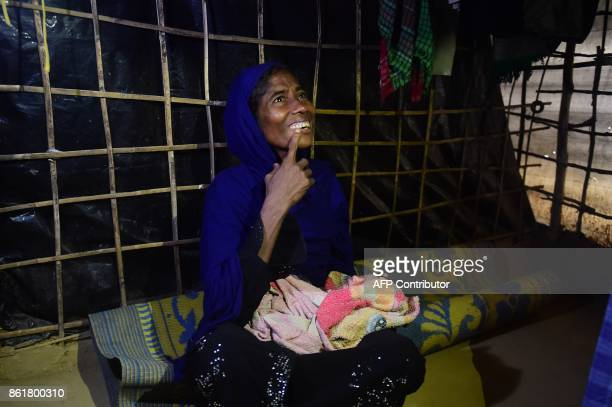 This picture taken on October 12 2017 shows Rohingya woman Fatima with her newborn grandson Mohammed Jubayed in his grandmother's lap in their house...
