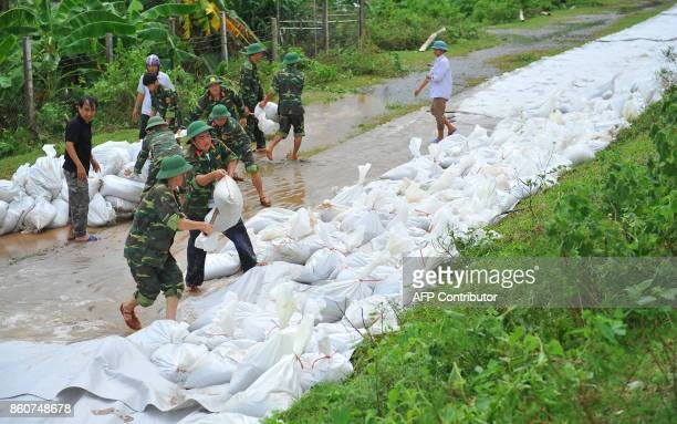This picture taken on October 12 2017 soldiers reinforcing a dyke with sand bags in the northern province of Ninh Binh The death toll from...