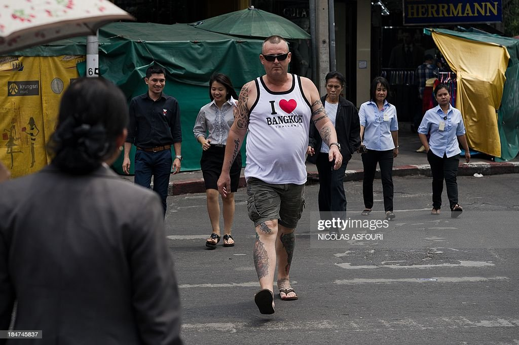 This picture taken on October 15, 2013 shows a tourist with tatoos and a t-shirt reading 'I love Bangkok' walking across a street in Bangkok. Thailand's central bank on October 16 left its benchmark interest rate unchanged at 2.5 percent, where it has been since May, after the economy slipped into a technical recession. AFP PHOTO/ Nicolas ASFOURI
