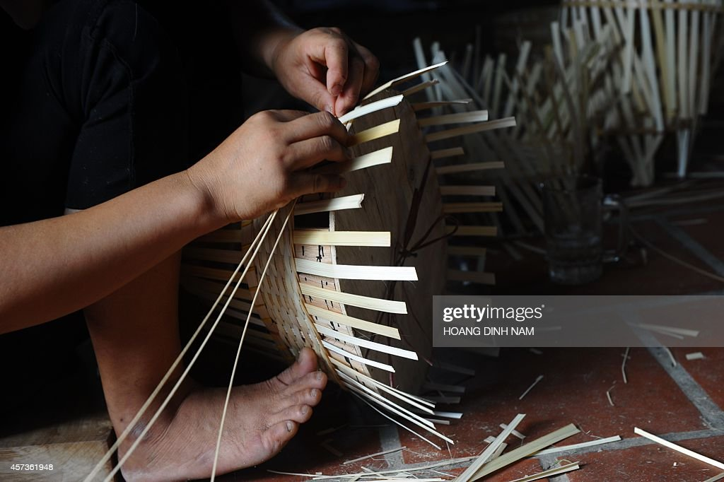 This picture taken on October 15 2014 shows women making bamboo flower baskets destined to export at a family workshop at Hong Van commune in the...