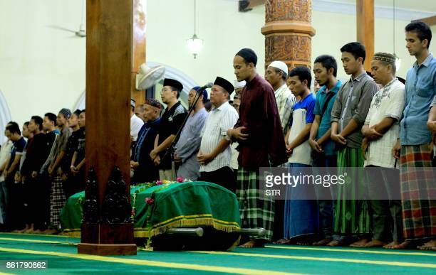 This picture taken on October 15 2017 shows family members and mourners performing performing funeral prayers behind a casket bearing the body of...