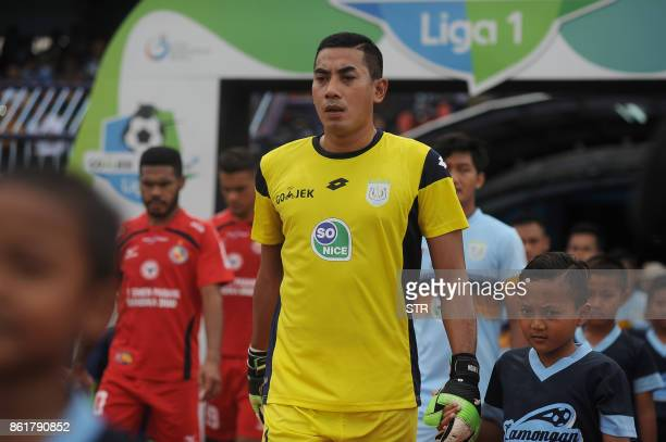 TOPSHOT This picture taken on October 15 2017 shows goalkeeper Choirul Huda of hometown club Persela in East Java making his way out with his team...