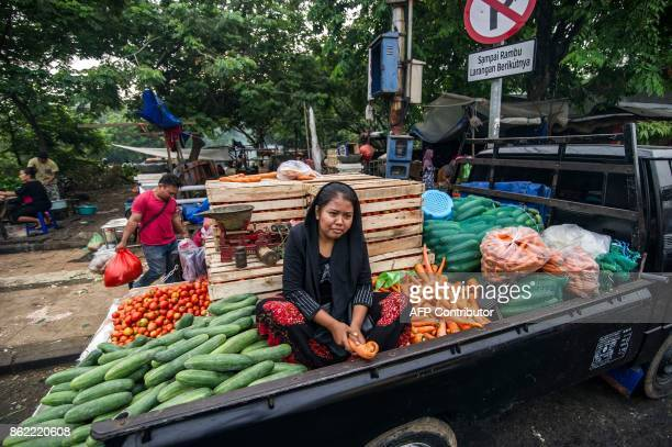 This picture taken on October 16 2017 shows a vendor selling vegetables from the back of a truck at a street market in Surabaya Indonesia's second...
