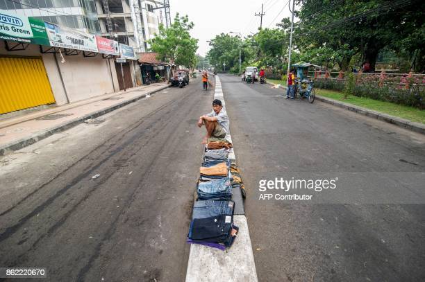 This picture taken on October 16 2017 shows a vendor selling products in the middle of a street beside a street market in Surabaya Indonesia's second...
