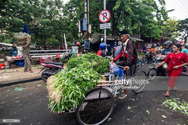 This picture taken on October 16 2017 shows a vendor transporting his produce to a street market in Surabaya Indonesia's second largest city / AFP...