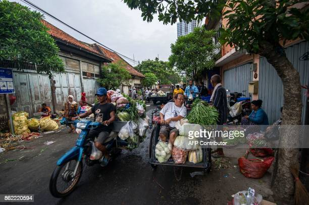This picture taken on October 16 2017 shows shoppers transporting their purchases home as vendors sell produce at a street market in Surabaya...