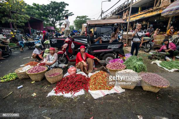 This picture taken on October 16 2017 shows vendors selling vegetables at a street market in Surabaya Indonesia's second largest city / AFP PHOTO /...