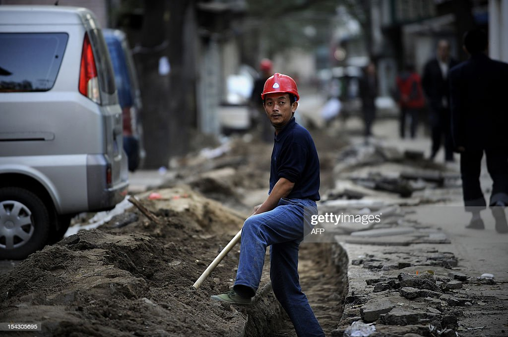 This picture taken on October 17, 2012 shows a Chinese worker shoveling by the side of a road in Beijing. China said on October 18 its economy grew 7.4 percent in the third quarter, easing for a seventh straight quarter, but the government and analysts said the data indicated it was stabilising.
