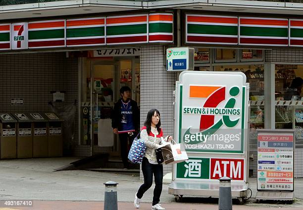 STORY 'JAPANECONOMYSHOPPINGMERGER' BY This picture taken on October 17 2015 shows a pedestrian walking past a store of Japan's largest convenience...