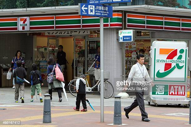 STORY 'JAPANECONOMYSHOPPINGMERGER' BY This picture taken on October 17 2015 shows pedestrians walking past a store of Japan's largest convenience...