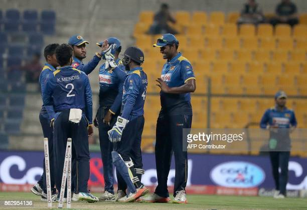 This picture taken on October 18 2017 shows Sri Lankan team celebrating after dismissing Upul Tharanga of Sri Lanka during the third one day...