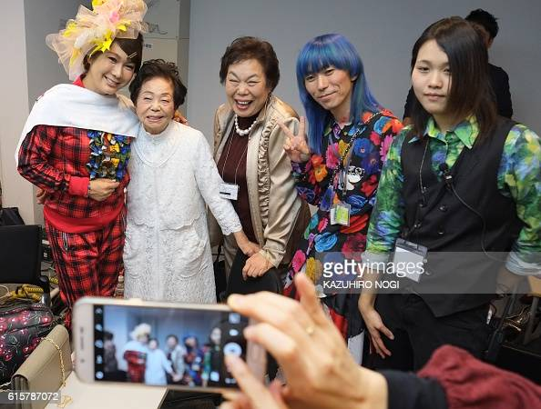 This picture taken on October 19 2016 shows model Miyo Maki designer Takafumi Tsuruta and supporters posing with models in a dressing room prior to...