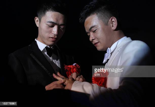 This picture taken on October 2 2012 shows Liu Wangqiang and his partner Lu Zhong exchanging wedding rings during their samesex public wedding...