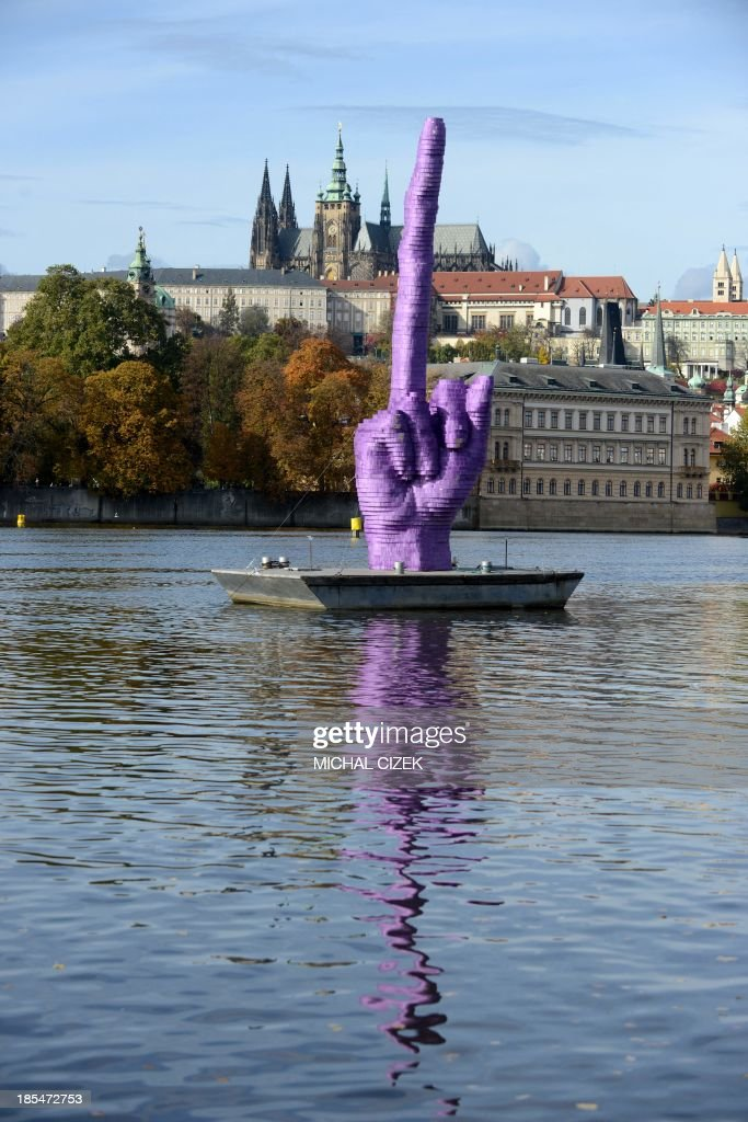 This picture taken on October 21, 2013 shows the giant purple middle finger sculpture by Czech artist David Cerny on Vltava River in Prague. This artwork installed today, four days before the Czech early general election, on the Vltava River is adressed to Czech president Milos Zeman who's residency is at Prague Castle (in background). AFP PHOTO /MICHAL CIZEK