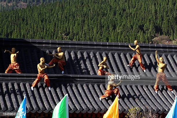This picture taken on October 22 2012 shows kungfu students performing on the rooftop of a Shaolin Temple to welcome guests at the 9th Zhengzhou...