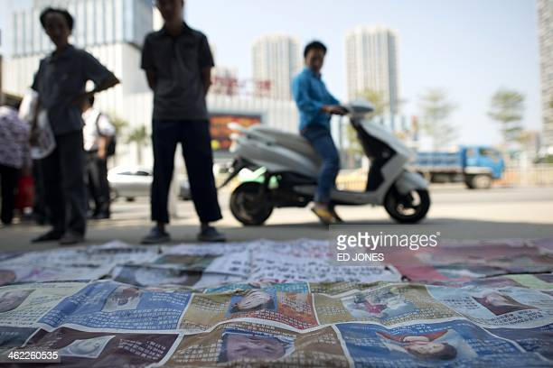 WITH 'CHINACHILDRENCRIMESOCIALFEATURE' BY This picture taken on October 23 2013 shows passerbys stopping to look at the pictures of missing children...