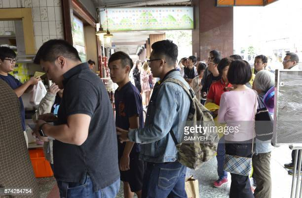 This picture taken on October 24 2017 shows people lining up outside the Jin Feng braised pork rice restaurant in Taipei From streetside stalls...