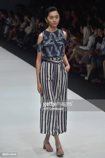 This picture taken on October 26 2017 shows Indonesian models presenting Indonesian traditional fabrics called Ikat by designer Didiet Maulana during...