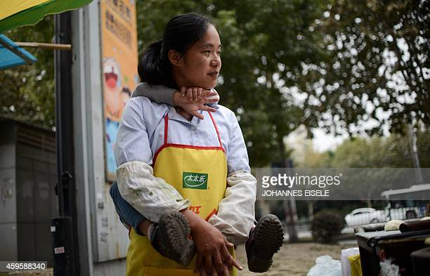 This picture taken on October 27 2014 shows sixyearold Pan Yulin who is from Hefei in Anhui province hugging his mother who is a street food vendor...