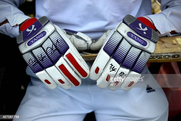 WITH 'CHINASPORTCRICKETCHN' BY This picture taken on October 3 2013 shows a Chinese cricketer's gloves and bat in Beijing Whiteclad Chinese...