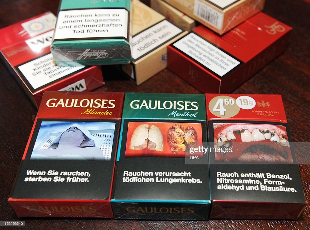 This picture taken on October 30, 2012 in Hamburg shows cigarette packages of various cigarette brands produced by tobacco company Reemtsma, one of the biggest tobacco and cigarette producers in Europe, showing pictures of diseases caused by smoking. AFP PHOTO / Angelika Warmuth