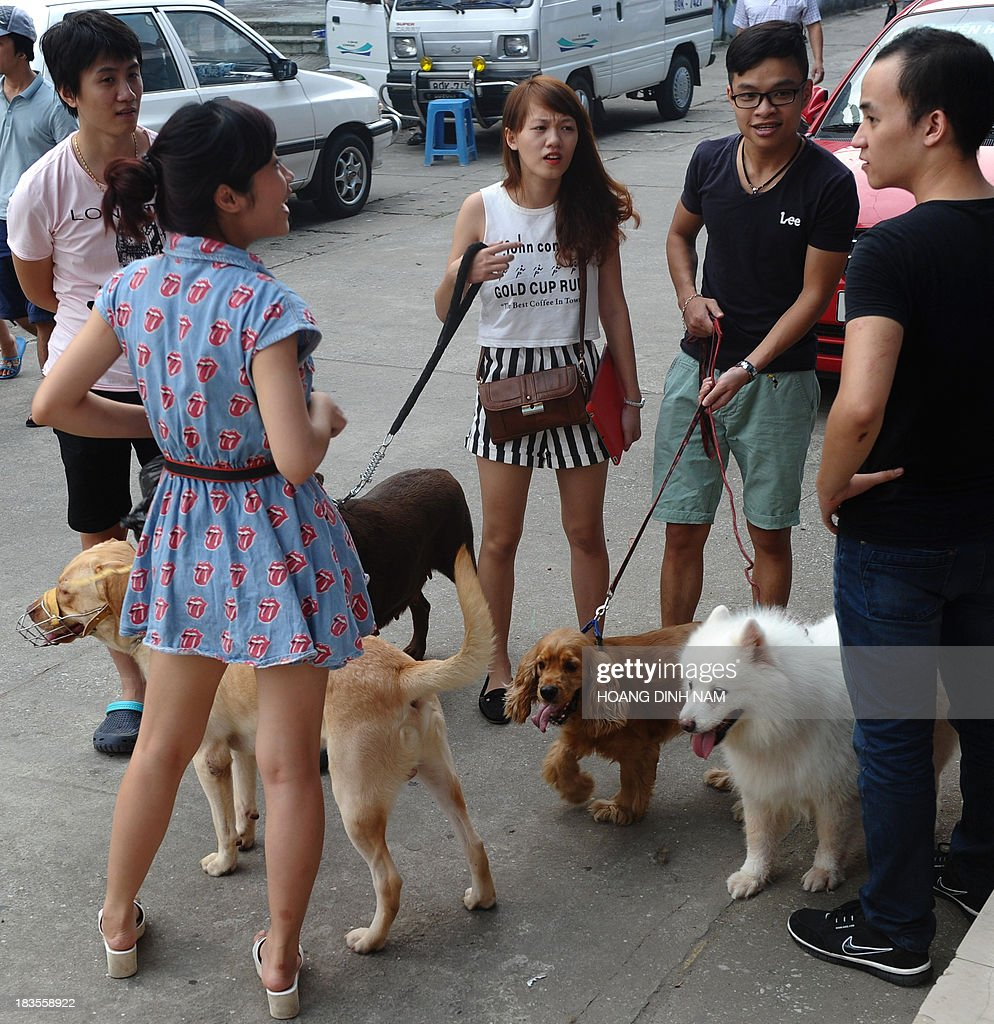 This picture taken on October 5, 2013 shows people with their pet dogs outside a dog show in Hanoi. Pet ownership in Vietnam has soared over the last 20 years as the middle class swelled since the Southeast Asian communist nation switched to a market economy in the early 1990s.