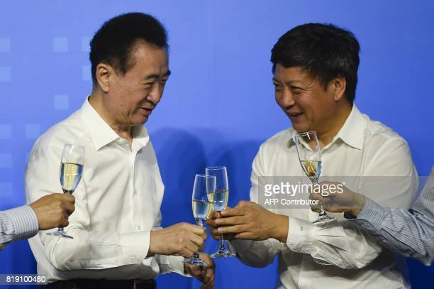 This picture taken on on July 19 2017 shows Chairman of China's Wanda Group Wang Jianlin sharing a toast with chairman of Sunac China Holdings...