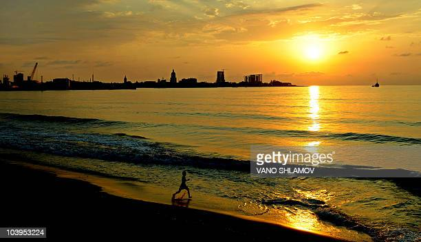 MAINVILLE* This picture taken on September 1 2010 shows a bather running into the sea at sunset over a beach in the town of Batumi On a lush strip of...