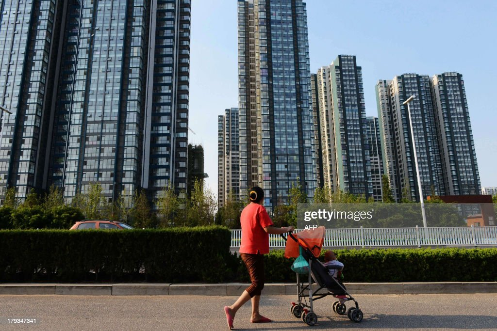This picture taken on September 1, 2013 shows a woman walking with a baby on the street in Qingdao, east China's Shandong province. China on September 2 lowered its figure for economic growth for last year to 7.7 percent from 7.8 percent, the National Bureau of Statistics said, in an unexpected downgrade for the key number. CHINA