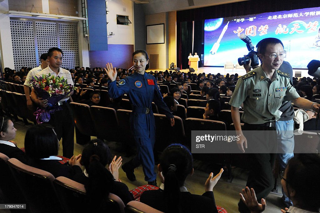 This picture taken on September 1, 2013 shows China's second female astronaut Wang Yaping (C) waving to students before delivering a lecture on the opening day of the high school affiliated to Beijing Normal University in Beijing. Wang Yaping finished her 15-day mission in space on June 26, 2013, after she and two other crew members were launched on the Shenzhou-10. CHINA