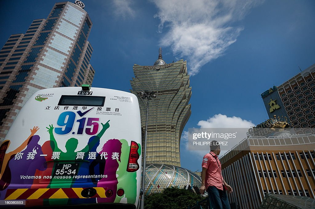 This picture taken on September 11, 2013 shows a man walking past a bus with election markings parked in front of the Grand Lisboa Casino (C) in Macau. Thousands in Macau, China's only gambling enclave, are to head to polling stations on September 15, 2013 for the city's fourth legislative election since its handover in 1999. AFP PHOTO / Philippe Lopez