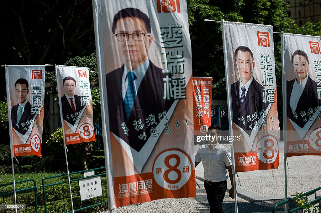 This picture taken on September 11, 2013 shows a man walking past election banners in Macau. Thousands in Macau, China's only gambling enclave, are to head to polling stations on September 15, 2013 for the city's fourth legislative election since its handover in 1999. AFP PHOTO / Philippe Lopez