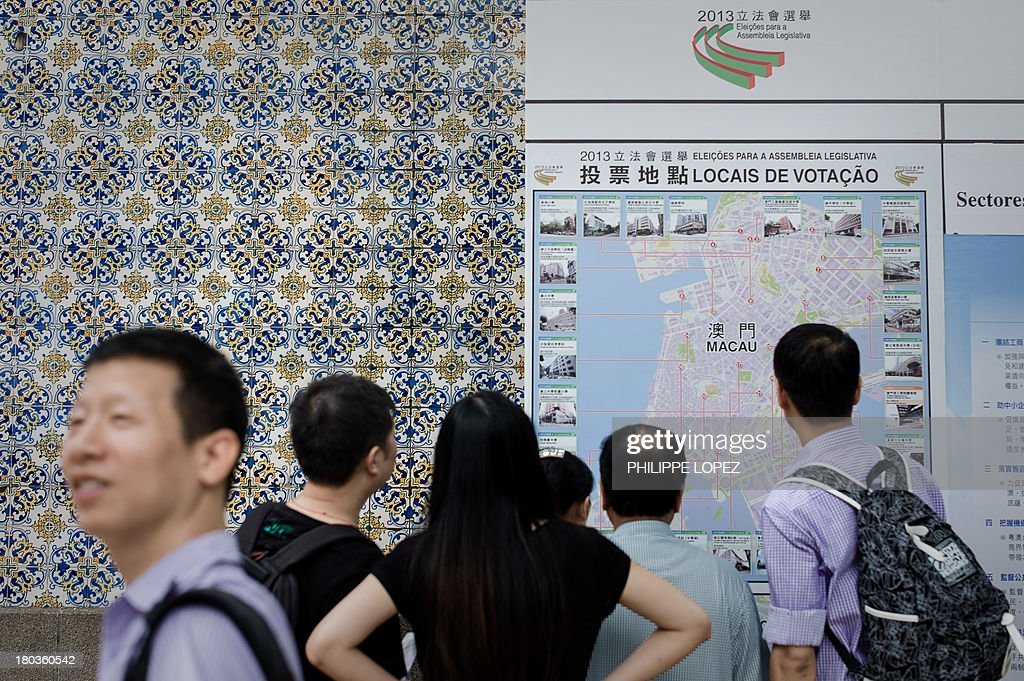 This picture taken on September 11, 2013 shows people looking at a map of a polling stations in Macau. Thousands in Macau, China's only gambling enclave, are to head to polling stations on September 15, 2013 for the city's fourth legislative election since its handover in 1999. AFP PHOTO / Philippe Lopez