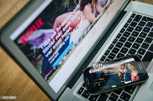 This picture taken on September 11 2014 shows the ondemand internet streaming media provider Netflix on a laptop screen and on a smartphone in...