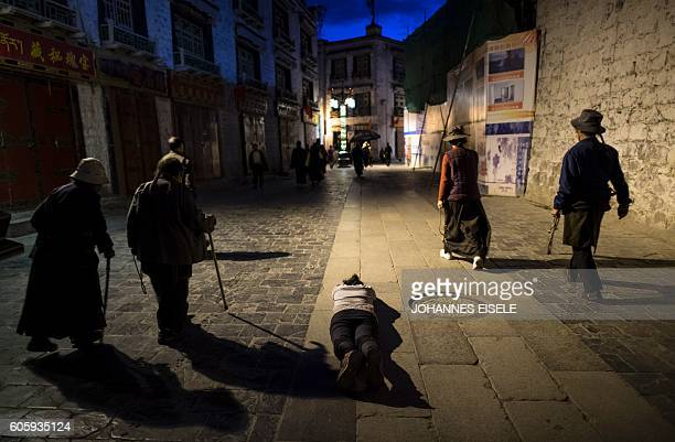TOPSHOT This picture taken on September 11 2016 shows a pilgrim praying and prostrating outside the Jokhang Temple in the regional capital Lhasa in...