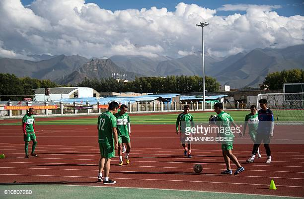 This picture taken on September 11 2016 shows members of the Lhasa Pureland Football Club kicking the ball during an official press meeting at their...