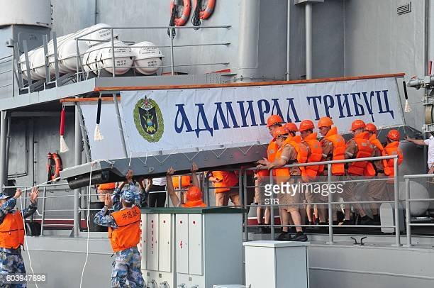 This picture taken on September 12 2016 shows sailors on the Russian destroyer Admiral Tributs lowering a gangway to Chinese sailors as they arrive...