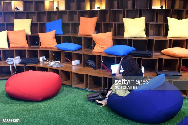 This picture taken on September 12 2017 shows a woman working at the EVHive event space a coworking space in Jakarta Bigname investors including...