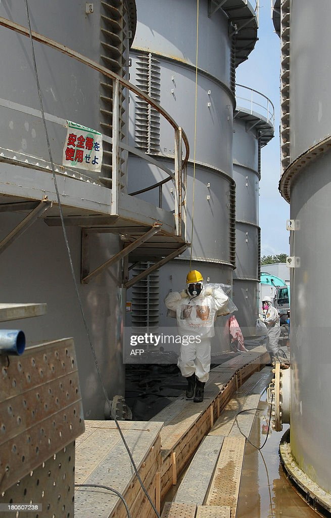 This picture taken on September 13 shows local government officials and nuclear experts inspecting a contamination water tank where radioactive materials were leaked at Tokyo Electric Power's (TEPCO) Fukushima Dai-ichi nuclear plant at Okuma town in Fukushima prefecture. The Japanese government and TEPCO were scrambling to reassure people on September 13 that they have a lid on Fukushima after a senior utility executive said the nuclear plant was 'not under control'.