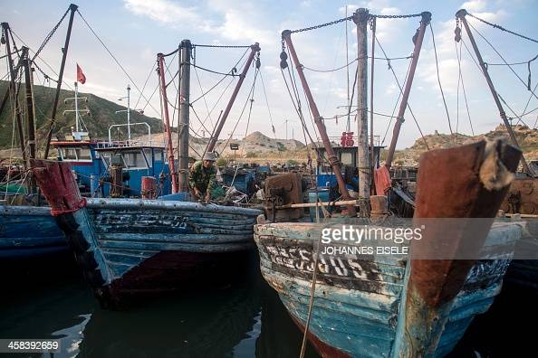 This picture taken on September 18 2016 shows fishing boats lining up at a pier in Xianrendao next to Yingkou City in China's northeastern Liaoning...