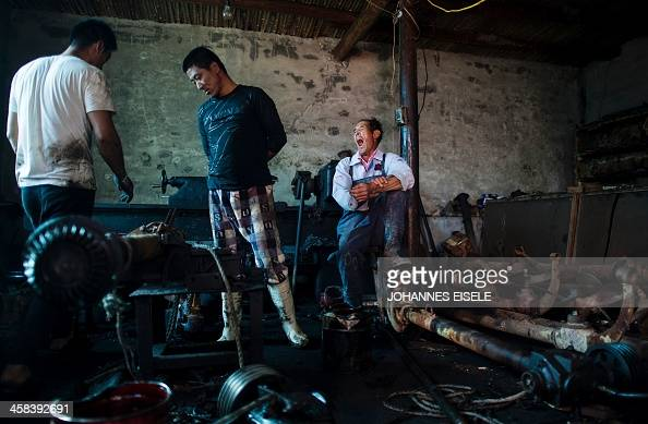 This picture taken on September 19 2016 shows Qin Yusheng waiting for a ship propeller being repaired in order to return it to the boat with his...