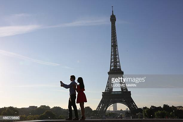 This picture taken on september 2 2015 at sunrise shows a couple taking a selfie picture in front of the Eiffel Tower in Paris AFP PHOTO / LUDOVIC...