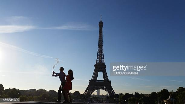 This picture taken on September 2 2015 at sunrise shows a couple spraying champagne in front of the Eiffel Tower in Paris AFP PHOTO / LUDOVIC MARIN