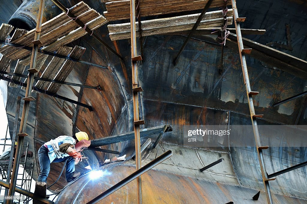 This picture taken on September 21 2015 shows a Chinese worker welding at a shipbuilding yard in Chongqing China is making efforts to establish...